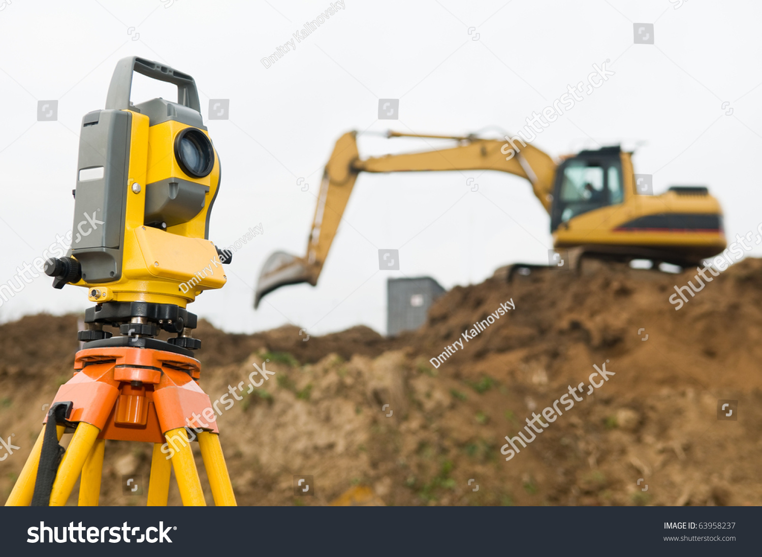 stock-photo-surveyor-equipment-theodolite-on-tripod-at-building-area-in-front-of-working-construction-machinery-63958237